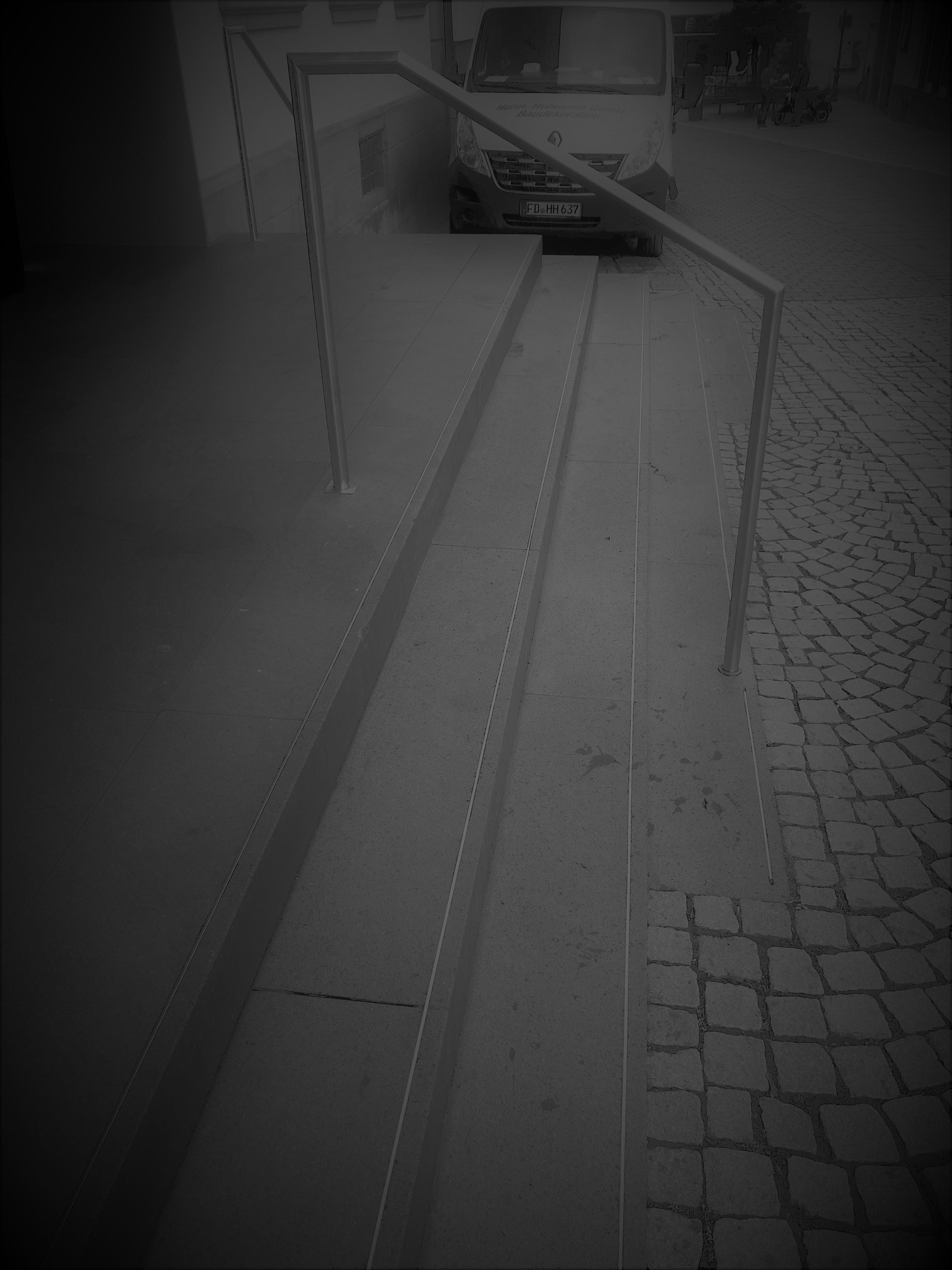 Dies ist ein Bild einer Treppe. Es wurde so verfremdet dass man nur noch schwarz-weis erkennen kann. Es wurde dunkel gemacht und unscharf. Es soll die Sicht von Sehbehinderten beispielhaft darstellen.